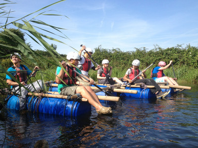 A group of Mentoring Plus' mentees participating in a raft race on a sunny day.